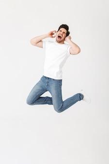 Obraz emocjonalnego podekscytowany młody człowiek pozowanie na białym tle nad białą ścianą słuchania muzyki ze skokami słuchawek.