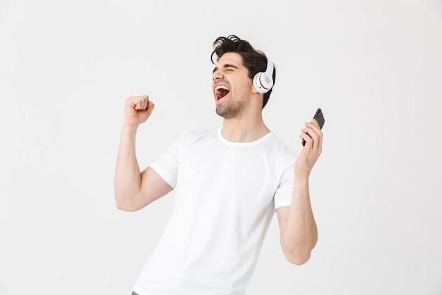 Obraz emocjonalnego podekscytowany młody człowiek pozowanie na białym tle nad białą ścianą słuchania muzyki ze śpiewem słuchawek.