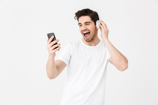 Obraz emocjonalnego podekscytowany młody człowiek pozowanie na białym tle nad białą ścianą słuchanie muzyki ze słuchawkami śpiewa przy użyciu telefonu komórkowego.