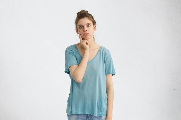 Obraz emocjonalnej młodej kobiety, która ma sfrustrowany wątpliwy wyraz twarzy, trzyma dłoń na twarzy, zastanawia się nad problemem, próbuje znaleźć najlepsze rozwiązanie, rozważa wszystkie zalety i wady, dmuchanie w policzki