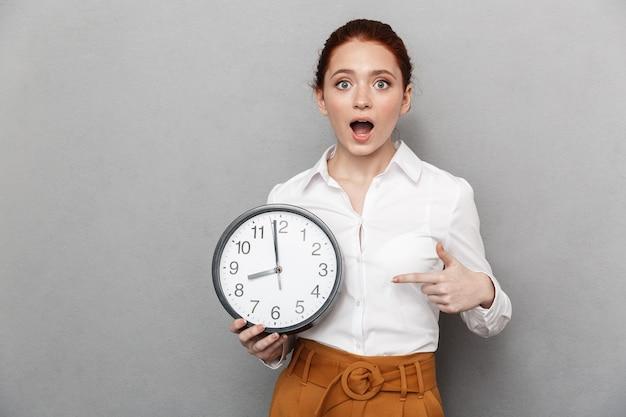 Obraz emocjonalnej rudowłosej bizneswoman 20s w formalnym stroju, zastanawiającej się, trzymając duży zegar na białym tle nad szarym