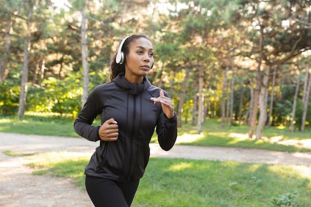 Obraz energicznej kobiety po dwudziestce w czarnym dresie i słuchawkach, ćwiczącej podczas biegania przez zielony park