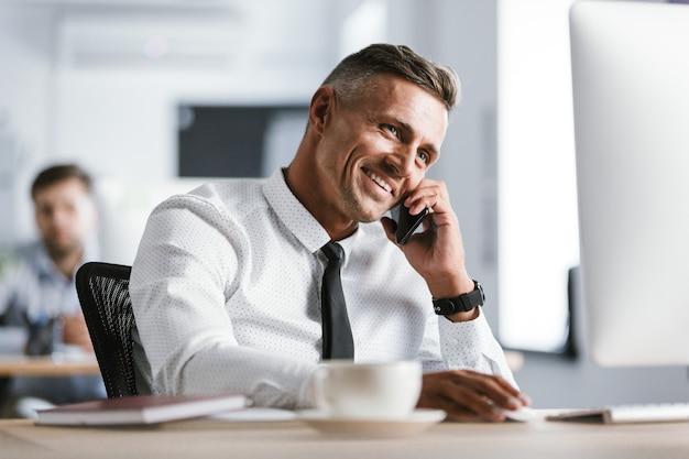 Obraz europejskiego dorosłego mężczyzny 30-tych w białej koszuli i krawacie, siedzącego przy biurku w biurze przy komputerze i mówiącego na smartfonie