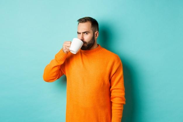 Obraz faceta pijącego kawę i patrzącego podejrzliwie w kamerę, patrzącego na coś dziwnego, stojącego w pomarańczowym swetrze na turkusowym tle