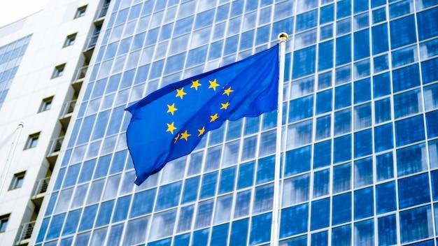 Obraz flagi ue powiewającej na wietrze przed biurowcem wysokiej firmy wykonanym z betonu i szkła. pojęcie ekonomii, rozwoju, rządu i polityki