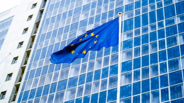 Obraz flagi unii europejskiej z staras na niebieskim tle przed wielkim nowoczesnym budynku biurowym. pojęcie gospodarki, rozwoju, rządu i polityki