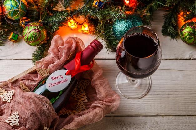 Obraz gałęzi jodłowych, bombek noworocznych, płonącej girlandy, butelki wina i szkła na białym stole