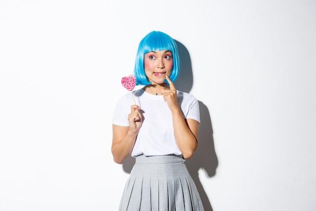 Obraz głupiej azjatki w niebieskiej peruce, przebranej na imprezę halloweenową, wyglądającej na zamyśloną, trzymającej cukierki w kształcie serca.