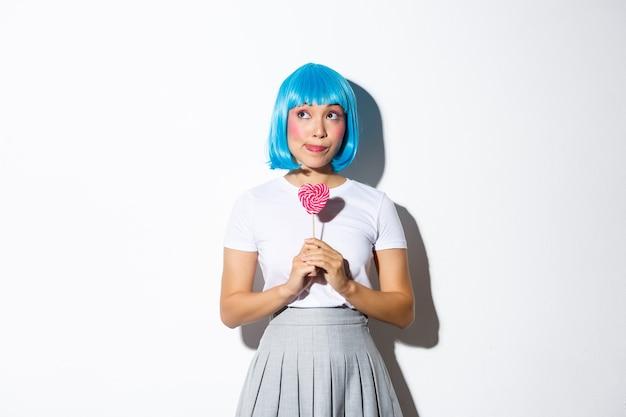 Obraz głupiej azjatki w niebieskiej peruce, wystrojonej na imprezę halloweenową, rozmarzonej patrząc w lewy górny róg, trzymającej cukierki w kształcie serca.
