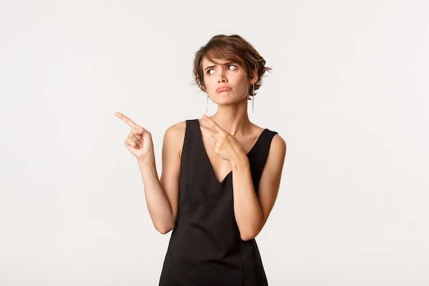 Obraz głupiej rozczarowanej kobiety w czarnej sukience wyglądającej na niezadowoloną, wskazującej palcami w lewo i dąsającej się niezadowolonej, stojącej nad bielą.