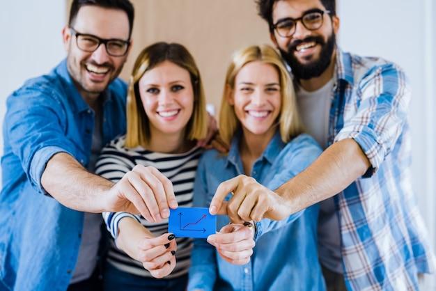 Obraz grupy osób trzymających razem kartę z rosnącym histogramem.