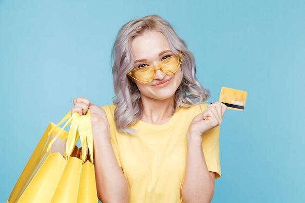 Obraz happy girl posiadania karty kredytowej i duże torby na zakupy isoleted nad niebieskim studio.