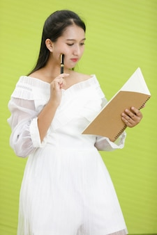 Obraz jest portretowy. asian uśmiechnięta pulchna kobieta na sobie białą sukienkę. lady asia stojąc i trzymając i patrząc na notebooka w zielonym tle.