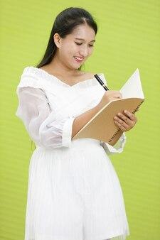 Obraz jest portretowy. asian uśmiechnięta pulchna kobieta na sobie białą sukienkę. lady asia stojąc i trzymając i pisząc na notebooku w zielonym tle.