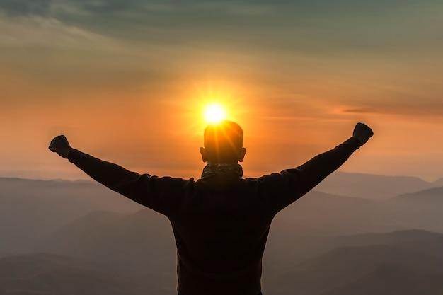 Obraz jest sylwetką. męska podróż widok górski przy wschodem słońca szczęśliwym.