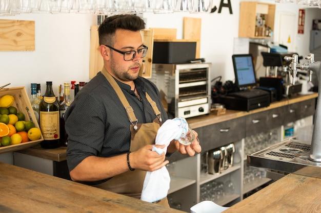 Obraz kelner czyszczenia kieliszek do wina w pubie. zawód, koncepcja stylu życia, praca.