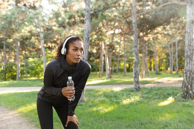 Obraz kobiecej kobiety w wieku 20 lat w czarnym dresie i słuchawkach, trzymającej butelkę wody podczas spaceru po zielonym parku
