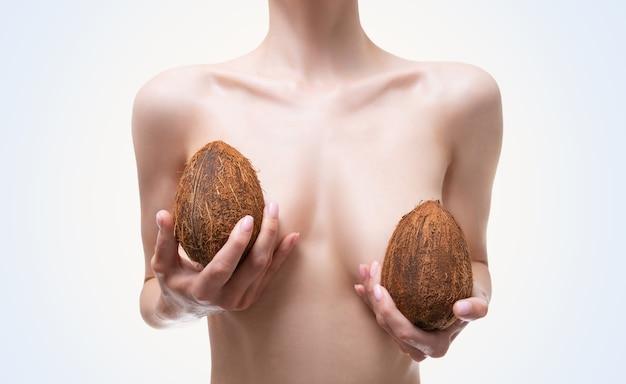 Obraz kobiecej piersi pokrytej kokosem. koncepcja chirurgii plastycznej. mammalogia. implanty silikonowe. różne środki przekazu