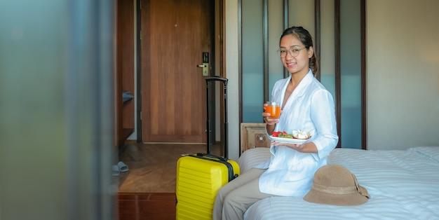 Obraz kobieta jedzenie owoców i pić sok pomarańczowy na łóżku w luksusowym pokoju hotelowym, koncepcja zdrowej żywności.