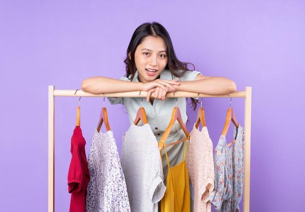 Obraz kobiety mody w spódnicy stojącej w pobliżu szafy z ubraniami i wybierającej, w co się ubrać, odizolowanej na fioletowym tle