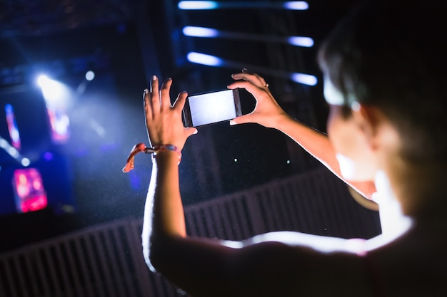Obraz kobiety nagrywającej występ muzyczny na koncercie festiwalowym