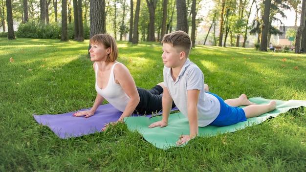 Obraz kobiety w średnim wieku nauczania nastoletniego chłopca robi joga i fitness na trawie w parku. rodzina dbająca o swoje zdrowie