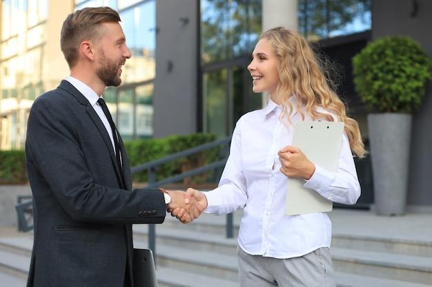Obraz kolegów omawiających dokumenty i uścisk dłoni w pobliżu biura.