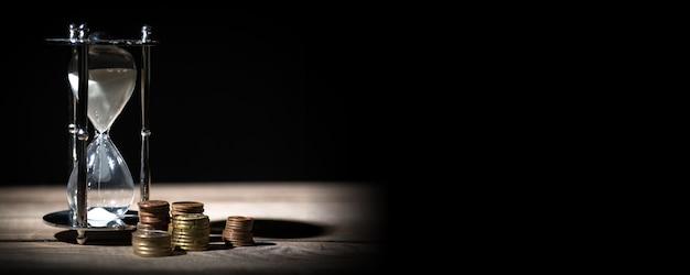Obraz koncepcji czasu i pieniędzy - zegarek z piaskiem i monety