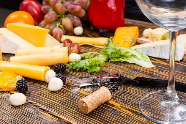 Obraz koncepcji wina i sera - zbliżenie pusty kieliszek do wina, otwieracz i korek na rustykalnym drewnianym stole otoczonym różnymi serami i owocami
