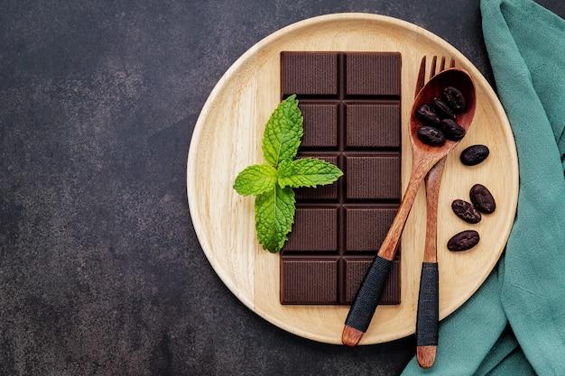 Obraz koncepcyjny żywności liści konopi z ciemną czekoladą i widelcem na ciemnym tle betonu.