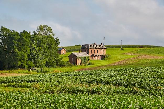 Obraz krajobrazu ujęcie rezydencji z czerwonej cegły z daleka z zielonymi polami uprawnymi na pierwszym planie i lasem na środku