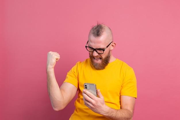 Obraz krzyczącego młodego, brodatego przystojnego mężczyzny świętującego zwycięstwo i sukces bardzo podekscytowany na różowo