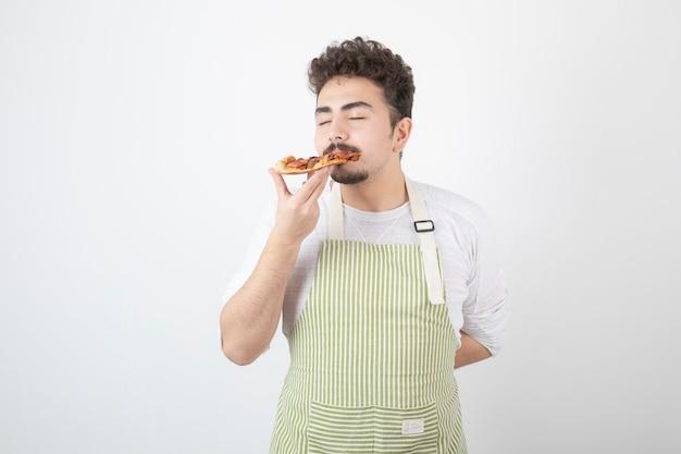 Obraz kucharza jedzącego kawałek pizzy na białym tle