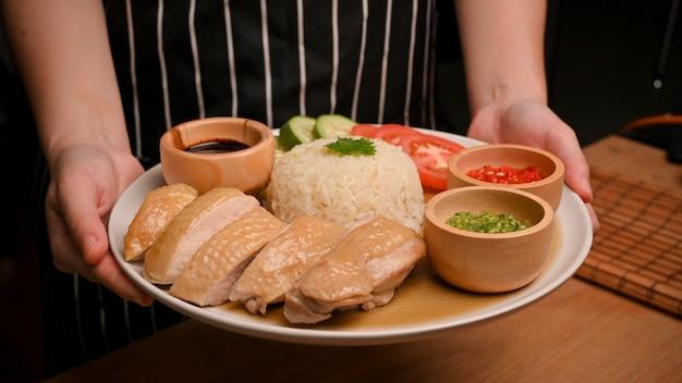 Obraz kuchni azjatyckiej. kelnerka podaje ryż z kurczaka hajnańskiego z sosem chili
