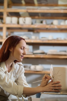 Obraz. ładna kobieta wyglądająca na zaangażowaną podczas malowania doniczki