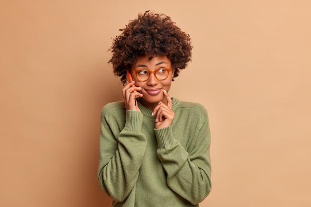 Obraz ładnie uśmiechniętej kobiety rozmawiającej przez telefon komórkowy z przyjaciółką omawiającej plany na weekendy skoncentrowana na szczęśliwym wyglądzie, nosi przezroczyste okulary i swobodny sweter