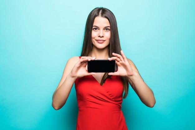 Obraz ładny całkiem młoda dama na białym tle nad niebieską ścianą. pokazujący wyświetlacz telefonu komórkowego.