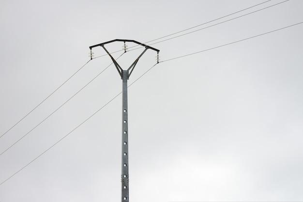 Obraz linii energetycznych słupa na tle szarego pochmurnego nieba