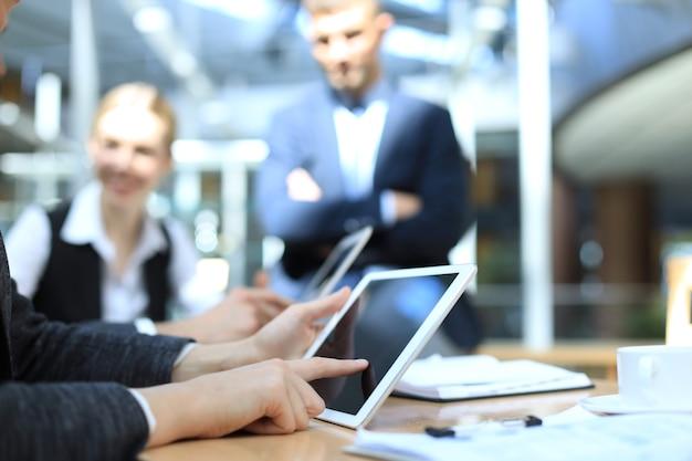 Obraz ludzkiej dłoni, wskazując na ekran dotykowy w środowisku pracy na spotkaniu.