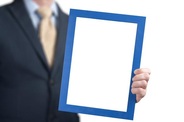 Obraz makiety. biznesmen trzyma pustą białą tablicę. człowiek ubrany w biznesową koszulę trzymając pustą ramkę. mężczyzna trzyma plakat makieta szablon z ramą na białym tle