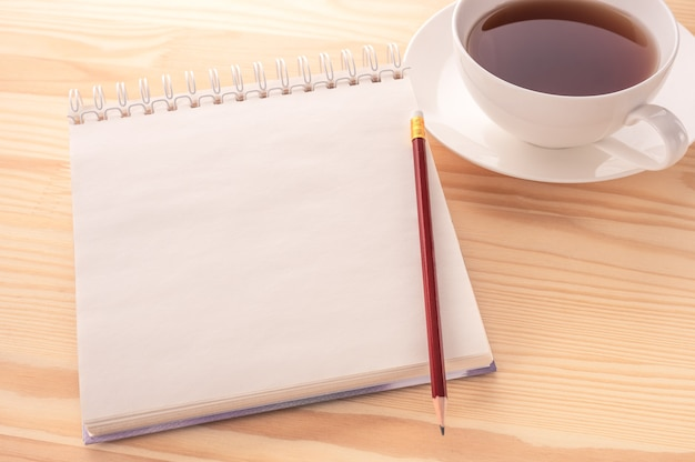 Obraz makiety. otwórz notatnik pustą stronę z miejsca na kopię i filiżankę herbaty na tle biały drewniany stół.