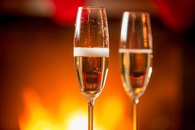 Obraz makro dwóch kieliszków wypełnionych musującym szampanem z płonącym kominkiem w tle