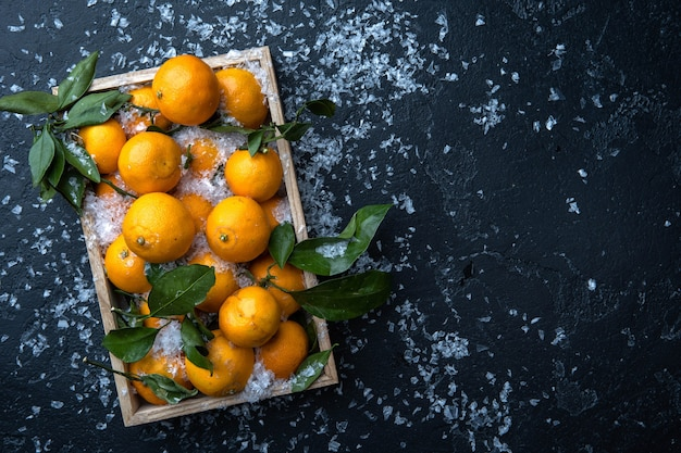 Obraz mandarynek w drewnianym pudełku na czarnym stole ze śniegiem