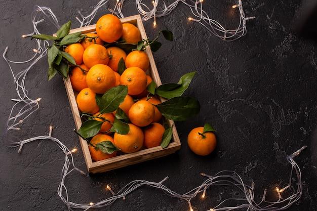 Obraz mandarynek w drewnianym pudełku z girlandą na czarnym stole