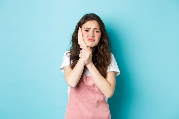 Obraz marszczącej brwi zdenerwowanej dziewczyny dotykającej opuchniętego policzka, cierpiącej na ból zęba, skarżącej się na próchnicę, stojącej na niebieskim tle, z potrzebą wizyty u dentysty.