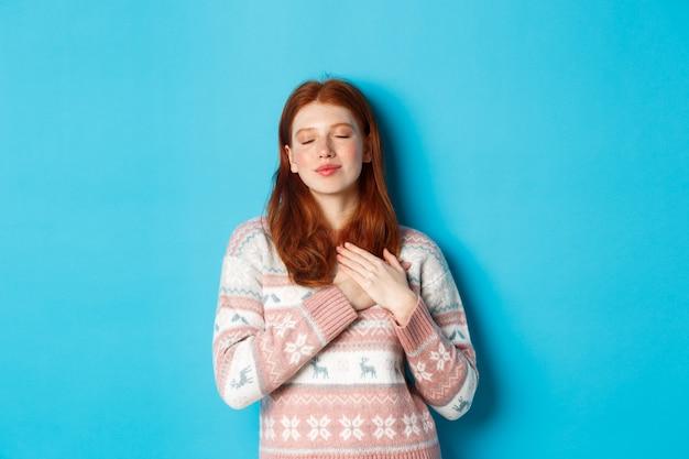 Obraz marzycielskiej rudowłosej dziewczyny, która zamyka oczy i trzyma ręce na sercu, czuje nostalgię, pamięta lub wyobraża sobie coś, stojącą na niebieskim tle.