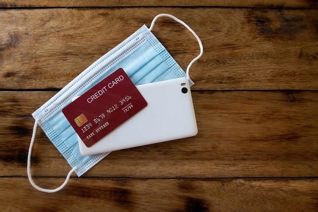 Obraz maski, telefonu komórkowego i karty kredytowej puste na drewnianym stole. widok z góry.