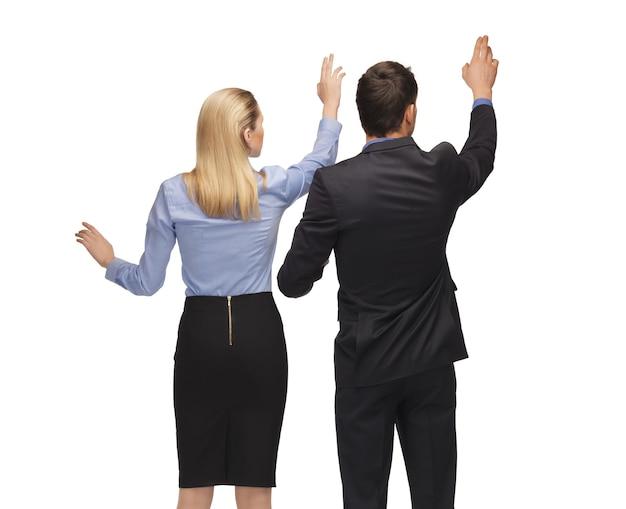 Obraz mężczyzny i kobiety pracujących z czymś wyimaginowanym.
