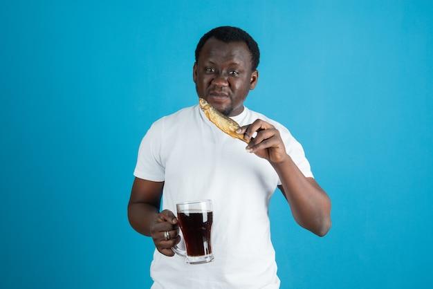 Obraz mężczyzny w białej koszulce trzymającego suszoną rybę ze szklanym kubkiem wina na tle niebieskiej ściany