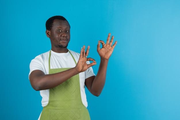 Obraz mężczyzny w zielonym fartuchu pokazującym ok gest na niebieskiej ścianie